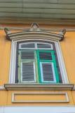 有绿色窗口的葡萄酒老黄色墙壁离开 老肮脏的风 免版税库存照片