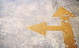 有黄色箭头的一条路在具体背景 库存照片