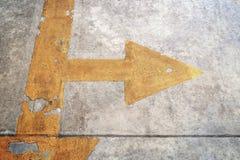 有黄色箭头的一条路在具体背景 库存图片