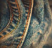 有黄色缝的螺纹的蓝色牛仔裤 库存照片