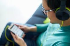 有绿色耳机的亚裔人听音乐播客电话 库存照片