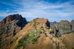 有绿色背包的妇女远足者走到Pico Ruivo远足 免版税库存照片