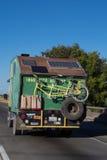 有黄色自行车的绿色露营车在后面 免版税库存照片