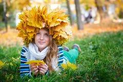 有黄色花圈的美丽的妇女在公园离开 免版税库存照片
