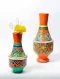 有黄色花的两个五颜六色的瓦器花瓶在白色backgroun 免版税库存照片