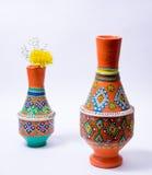 有黄色花的两个五颜六色的瓦器花瓶在白色backgroun 图库摄影