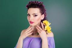 有紫色花的俏丽的女孩在头发缠绕 免版税库存图片
