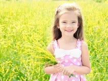 有黄色花的可爱的微笑的小女孩在草甸 免版税库存照片