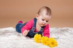 有黄色花的小婴儿婴孩 免版税图库摄影