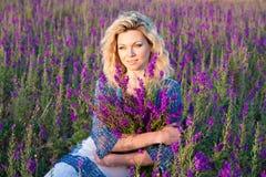 有紫色花的白肤金发的妇女 免版税库存照片