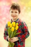 有黄色花花束的微笑的男孩  库存图片