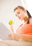 有绿色苹果读书报纸的妇女在家 免版税库存照片