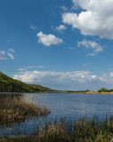 有黄色草在前景和蓝天的一个美丽的蓝色湖与云彩 图库摄影