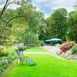有绿色草坪和花床的夏天公园 免版税库存照片
