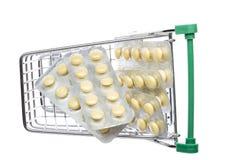有黄色药片的商店推车在天线罩包装 库存图片