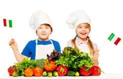 有绿色菜的愉快的年轻意大利人厨师 免版税图库摄影