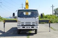 有黄色起重机胳膊的白色五十铃平板车卡车在停车场-俄罗斯,莫斯科, 2016年8月30日 免版税库存照片