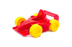 有黄色轮子的塑料红色赛跑的玩具汽车玩具 免版税库存图片