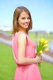 有黄色郁金香的微笑的女孩 库存照片