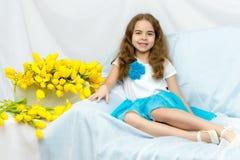 有黄色郁金香的美丽的白肤金发的女小学生坐cou 库存图片