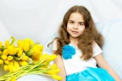 有黄色郁金香的美丽的白肤金发的女小学生坐cou 库存照片