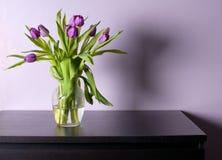 有紫色郁金香的花瓶在黑桌 库存照片
