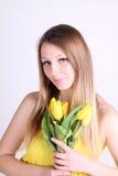 有黄色郁金香的长发浪漫女孩 免版税图库摄影