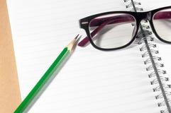 有绿色铅笔、镜片和被排行的页的空的笔记本 库存照片