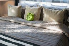有绿色闹钟和枕头的卧室在床上 免版税库存图片