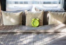 有绿色闹钟的卧室在床上 免版税库存图片