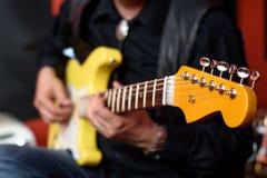 有黄色防御者电吉他的吉他弹奏者 免版税图库摄影