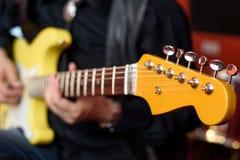 有黄色防御者风俗的吉他弹奏者 图库摄影