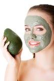 有绿色鲕梨黏土脸面护理面具的美丽的妇女 库存图片