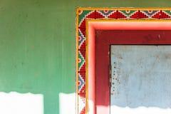 有绿色,红色和黄色颜色的西藏装饰墙壁与宗师在纳姆奇的仁波切寺庙阳光  锡金,印度 免版税库存照片