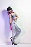 有紫色头发的性感的女孩和在摆在灰色背景的身体的纹身花刺 灰色牛仔裤和T恤杉的完善的妇女,明亮 免版税图库摄影