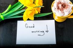 有黄色黄水仙的咖啡杯开花并且引述在白色土气桌上的早晨好 母亲节或妇女天 2007个看板卡招呼的新年好 T 免版税库存照片