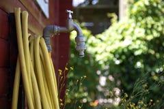 有黄色水管的龙头在红色庭院棚子旁边 库存图片