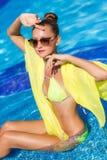 有黄色pareo的一个苗条女孩由水池 库存图片