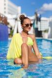 有黄色pareo的一个苗条女孩由水池 图库摄影