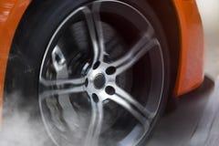 有细节的橙色跑车在做烧坏的转动的和抽烟的轮子/轮胎 免版税图库摄影