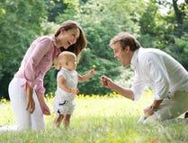 有给花的孩子的愉快的家庭父亲 库存图片