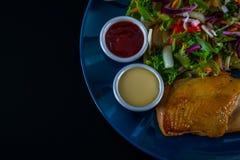 有莴苣混合和两个调味汁的,蓝色板材烤鸡乳房 免版税库存图片