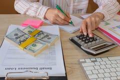 有经营计划、计算器、美元钞票、spreadshee和笔的女性在桌上 免版税库存照片