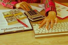 有经营计划、计算器、美元钞票、spreadshee和笔的女性在桌上 免版税图库摄影