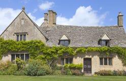 有紫藤的传统英国石灰石房子在乡村 免版税库存图片