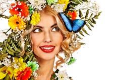 有蝴蝶和花的妇女。 库存照片
