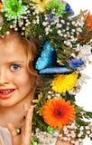 有蝴蝶和花的孩子。 库存图片