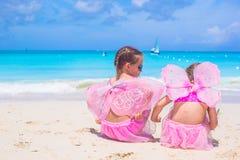 有蝴蝶的小女孩在海滩夏天飞过 免版税图库摄影
