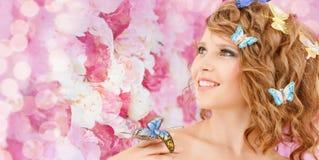 有蝴蝶的愉快的十几岁的女孩在头发 免版税库存照片