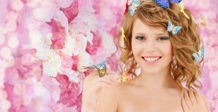 有蝴蝶的愉快的十几岁的女孩在头发 图库摄影